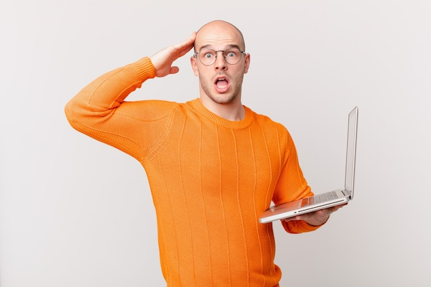 Łysy mężczyzna z komputerem wyglądający na szczęśliwego, zdziwionego i zdziwionego, uśmiechnięty i uświadomił sobie niesamowite i niewiarygodnie dobre wieści