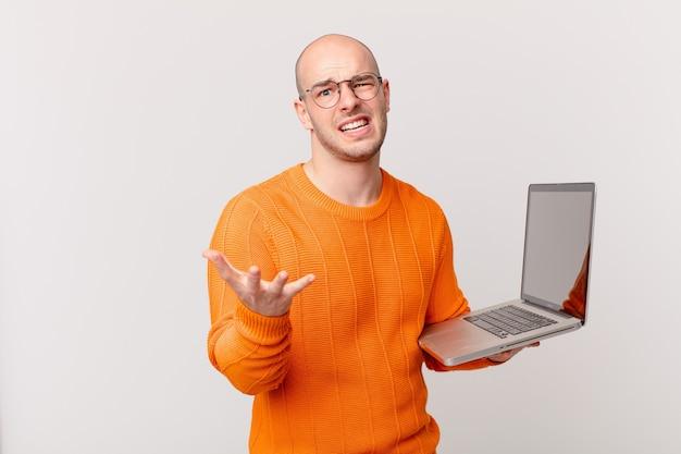 Łysy mężczyzna z komputerem wyglądający na zdesperowanego i sfrustrowanego, zestresowanego, nieszczęśliwego i zirytowanego, krzyczącego i krzyczącego