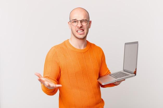 Łysy mężczyzna z komputerem wyglądający na złego, zirytowanego i sfrustrowanego, krzyczącego wtf lub co jest z tobą nie tak