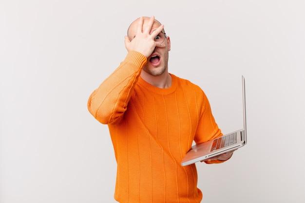 Łysy mężczyzna z komputerem wyglądający na zszokowanego, przestraszonego lub przerażonego, zakrywający twarz dłonią i zerkający między palcami