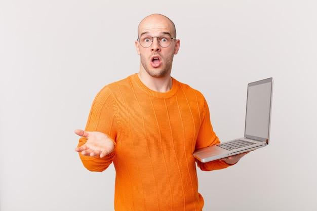 Łysy mężczyzna z komputerem z otwartymi ustami i zdumiony, zszokowany i zdumiony niewiarygodną niespodzianką