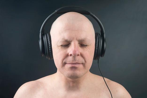 Łysy mężczyzna z zamkniętymi oczami słucha muzyki przez słuchawki na ciemnym tle