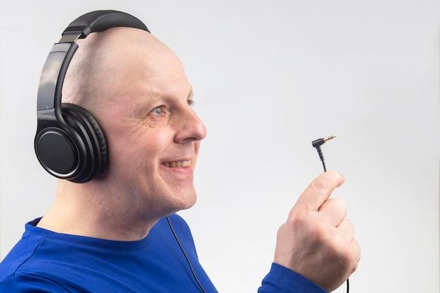 Łysy mężczyzna ze słuchawkami na głowie i otwartą wtyczką w ręku na białym tle