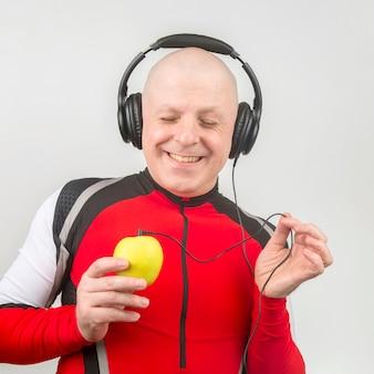 Łysy mężczyzna ze słuchawkami słucha muzyki przez odtwarzacz żółtych jabłek