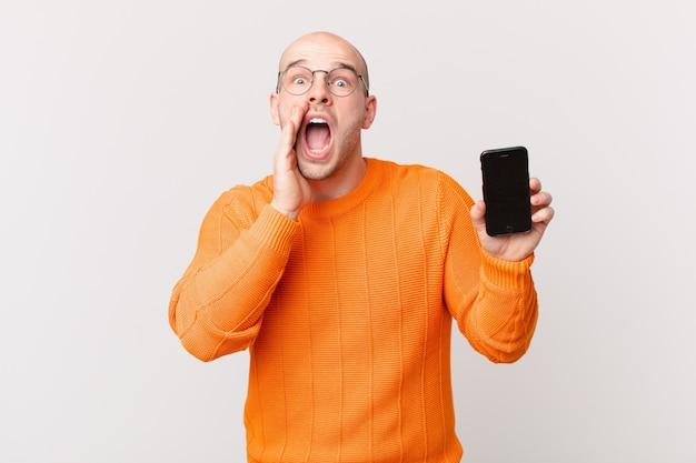 Łysy mężczyzna ze smartfonem czuje się szczęśliwy