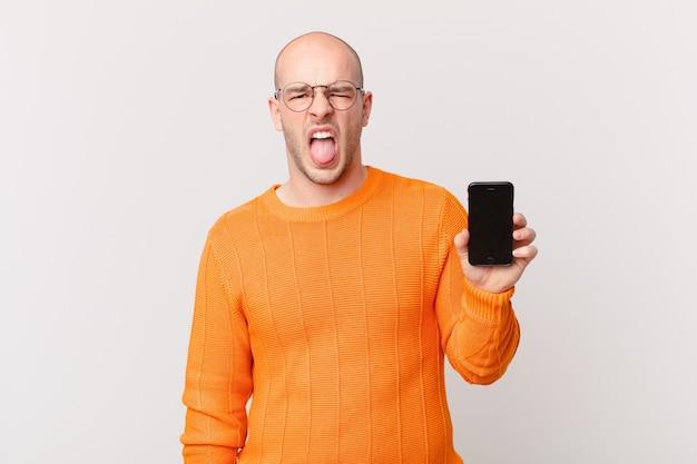 Łysy mężczyzna ze smartfonem czuje się zniesmaczony i zirytowany, wystawia język, nie lubi czegoś paskudnego i obrzydliwego