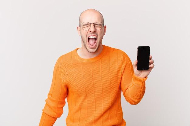 """Łysy mężczyzna ze smartfonem krzyczy agresywnie, wygląda na bardzo rozgniewanego, sfrustrowanego, oburzonego lub zirytowanego, krzyczy """"nie"""""""