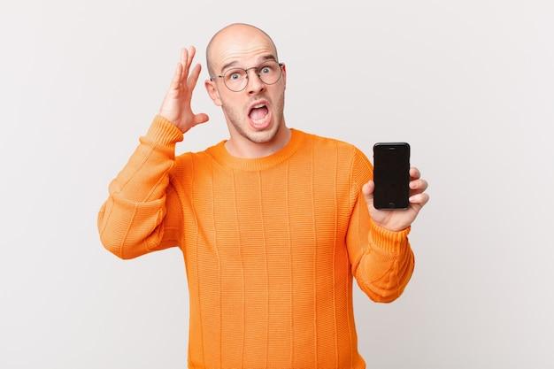 Łysy mężczyzna ze smartfonem krzyczy z rękami w górze, czuje się wściekły, sfrustrowany, zestresowany i zdenerwowany