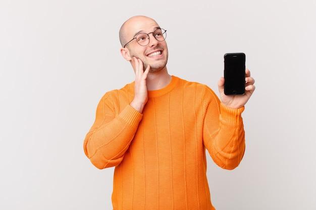 Łysy mężczyzna ze smartfonem przy izolowanej ścianie