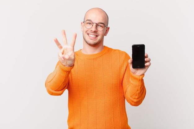 Łysy mężczyzna ze smartfonem uśmiechnięty i wyglądający przyjaźnie, pokazujący numer trzy lub trzeci z ręką do przodu, odliczający w dół