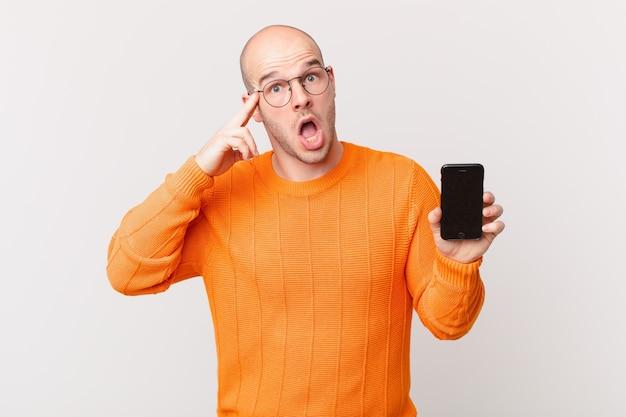Łysy mężczyzna ze smartfonem wyglądający na zaskoczonego, z otwartymi ustami, zszokowanego, realizującego nową myśl, pomysł lub koncepcję