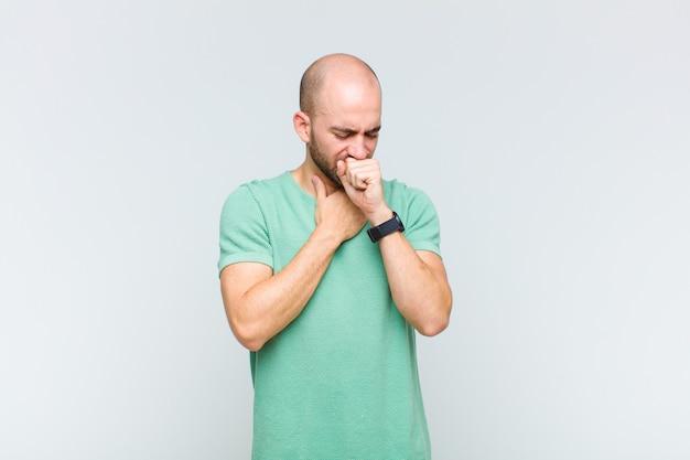 Łysy mężczyzna źle się czuje z bólem gardła i objawami grypy, kaszle z zakrytymi ustami