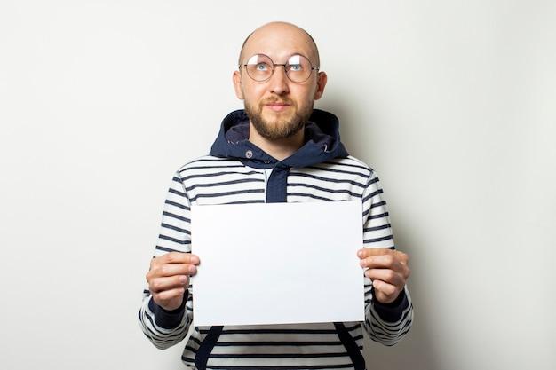 Łysy młody człowiek z brodą w okularach, sweter z kapturem trzyma przed sobą pustą kartkę papieru z spojrzeniami na białym tle. skopiuj miejsce