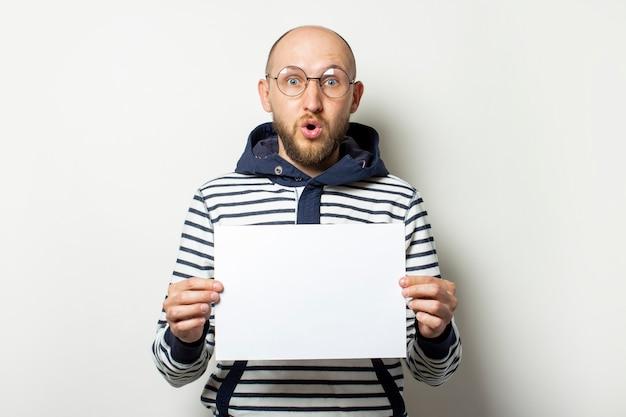 Łysy młody człowiek z brodą w okularach, sweter z kapturem trzymający przed sobą pusty arkusz papieru z zaskoczoną twarzą na białym tle. skopiuj miejsce