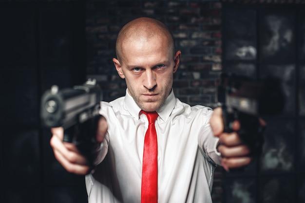 Łysy najemny zabójca w czerwonym krawacie mierzy w pistolety
