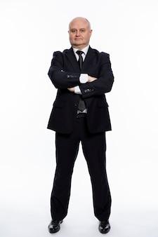 Łysy, poważny mężczyzna w średnim wieku, w surowym czarnym garniturze, stoi z rękami skrzyżowanymi na piersi. styl biznesowy i korporacyjny. pełna wysokość. białe tło. pionowa linia.