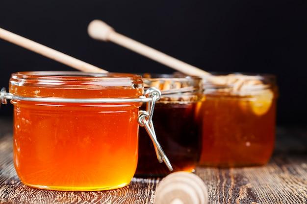 Łyżka do miodu wraz z wysokiej jakości miodem pszczelim, stary stół na którym stoi zdrowy i słodki miód pszczeli oraz specjalna drewniana łyżka