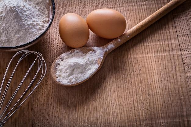 Łyżka miska z jajkami mąki corolla na desce żywności i