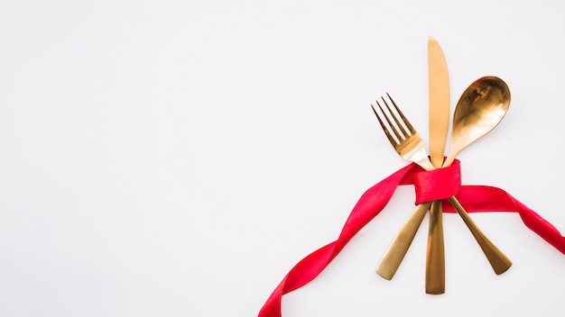 Łyżka, nóż i widelec z czerwoną wstążką