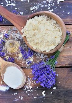 Łyżka pełna płatków mydła z olejkiem i kilka kwiatów lawendy i wodorowęglanu sodu na drewniane tła
