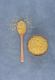 Łyżka ryżu i miska ryżu na marmurowym tle.