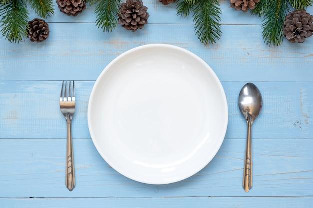 Łyżka, widelec i pusty talerz z bożego narodzenia dekoracji