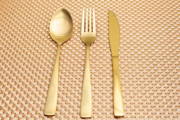 Łyżka, widelec, nóż w kolorze złotym