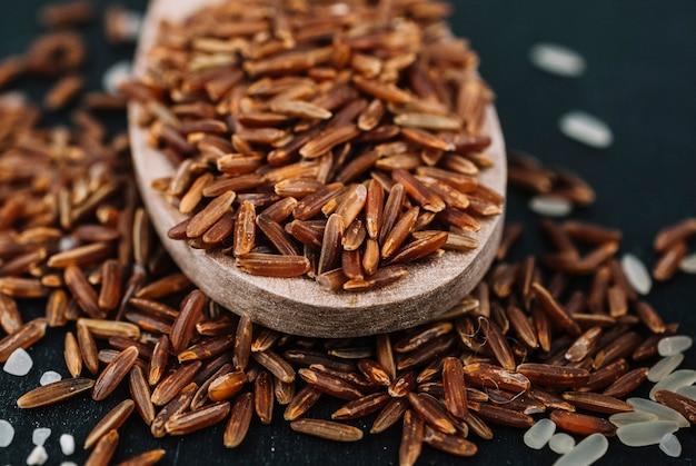 Łyżka z brązowym ryżem na rozlanych ziarnach