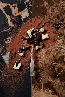 Łyżka z czekoladą i syropem czekoladowym na ciemnym marmurowym tle