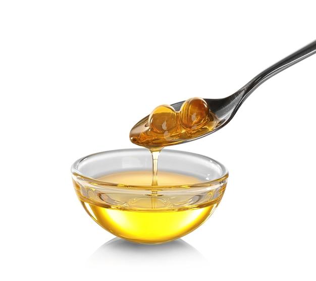 Łyżka z kapsułkami żelatynowymi i szklaną miseczką oleju z wątroby dorsza