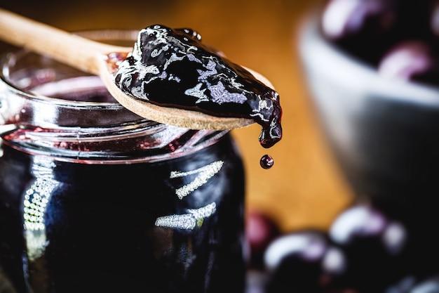 Łyżka z kroplą dżemu jabuticaba kapiącego i opadającego, egzotyczne winogrono z ameryki łacińskiej używane w słodyczach w ameryce