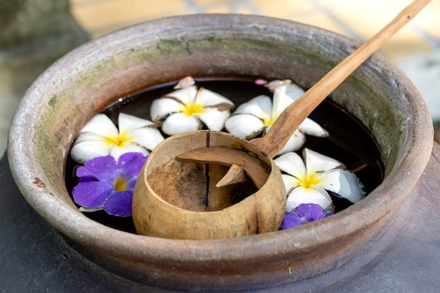 Łyżkę z łupin orzecha kokosowego i gliniany słój wypełniony wodą wraz z kwiatami. tajlandia. ścieśniać