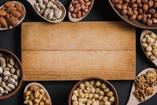 Łyżki i miski z orzechami leżące wokół planszy