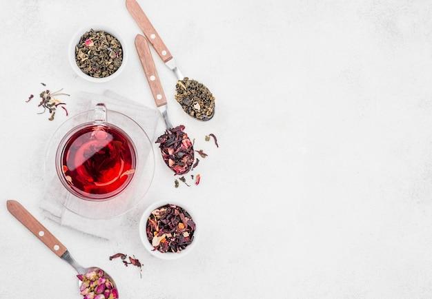 Łyżki z ziołami i kubek z herbatą z miejsca na kopię
