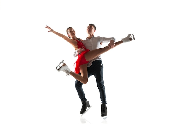 Łyżwiarstwo figurowe na białym tle. dwóch sportowców ćwiczących i trenujących w akcji i ruchu. pełen wdzięku i nieważkości. pojęcie ruchu, sportu, piękna.
