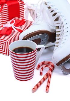 Łyżwy figurowe z filiżanką kawy na białym tle