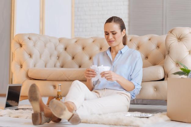 Łzy. nieszczęśliwa młoda emocjonalna kobieta siedzi na podłodze i płacze, łząc i drapiąc kartkę papieru