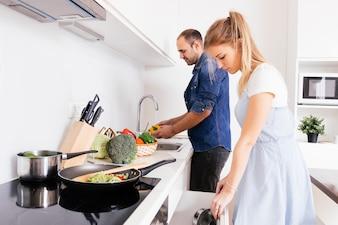 Mąż pomaga jej blondynki młodej żonie przygotowywa jedzenie w kuchni