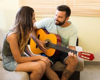 Mężczyzna bawić się gitarę dla jego pięknej żony w domu