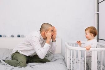 Mężczyzna bawić się z uśmiechniętym małym dzieckiem w ściąga w sypialni