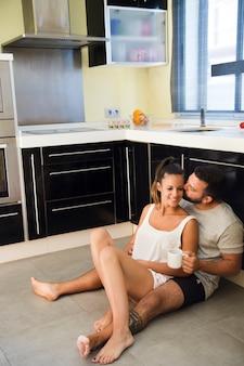 Mężczyzna całuje jego żony w kuchni