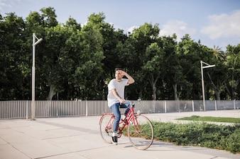 Mężczyzna cyklista osłania jego oko podczas jazdy na rowerze