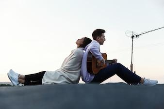 Mężczyzna gra na gitarze, podczas gdy jego kobieta pochyla się nad nim czule na dachu