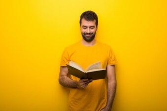 Mężczyzna na odosobnionym wibrującym żółtym kolorze trzyma książkę i cieszy się czytanie