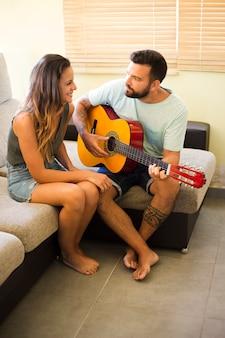 Mężczyzna obsiadanie na kanapie bawić się gitarę dla jego żony
