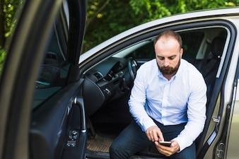 Mężczyzna obsiadanie w samochodzie z otwarte drzwi patrzeje telefonu komórkowego ekran