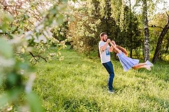 Mężczyzna podnosi jego córki w parku