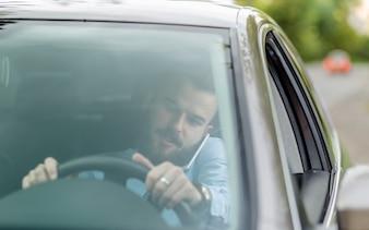 Mężczyzna siedzący wewnątrz samochodu rozmawia przez telefon komórkowy widziane przez windscreen