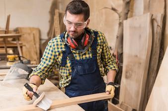 Męski cieśla czyści drewnianą deskę z muśnięciem w warsztacie