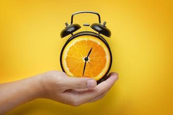 Męski ręki mienia budzik Pomarańczowa owoc na Żółtym tle